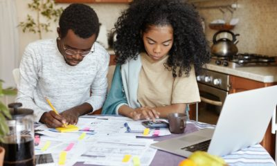 African man and woman sitting at kitchen table with papers and laptop pc, managing domestic finances