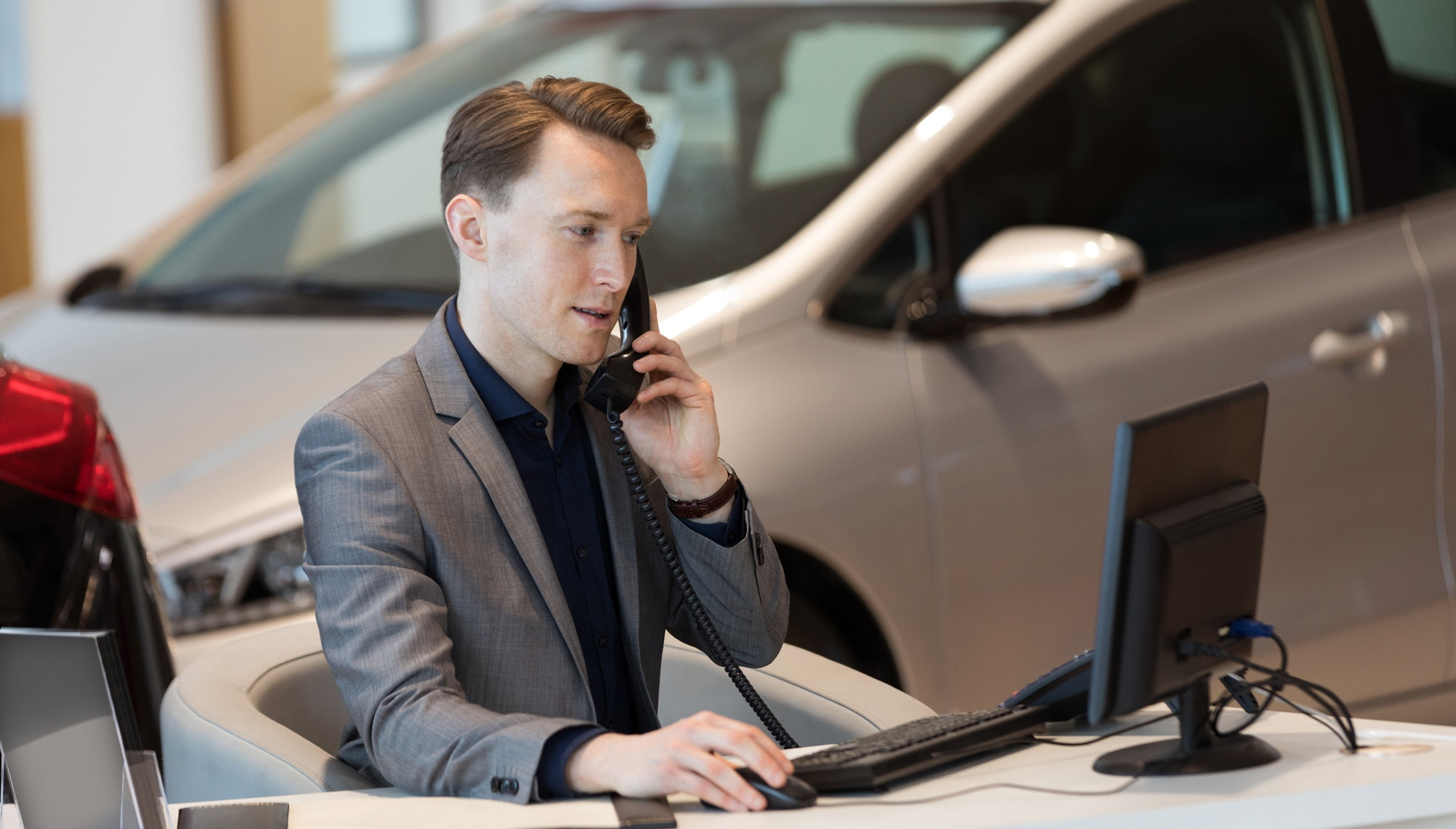 Sales talking on phone while using computer