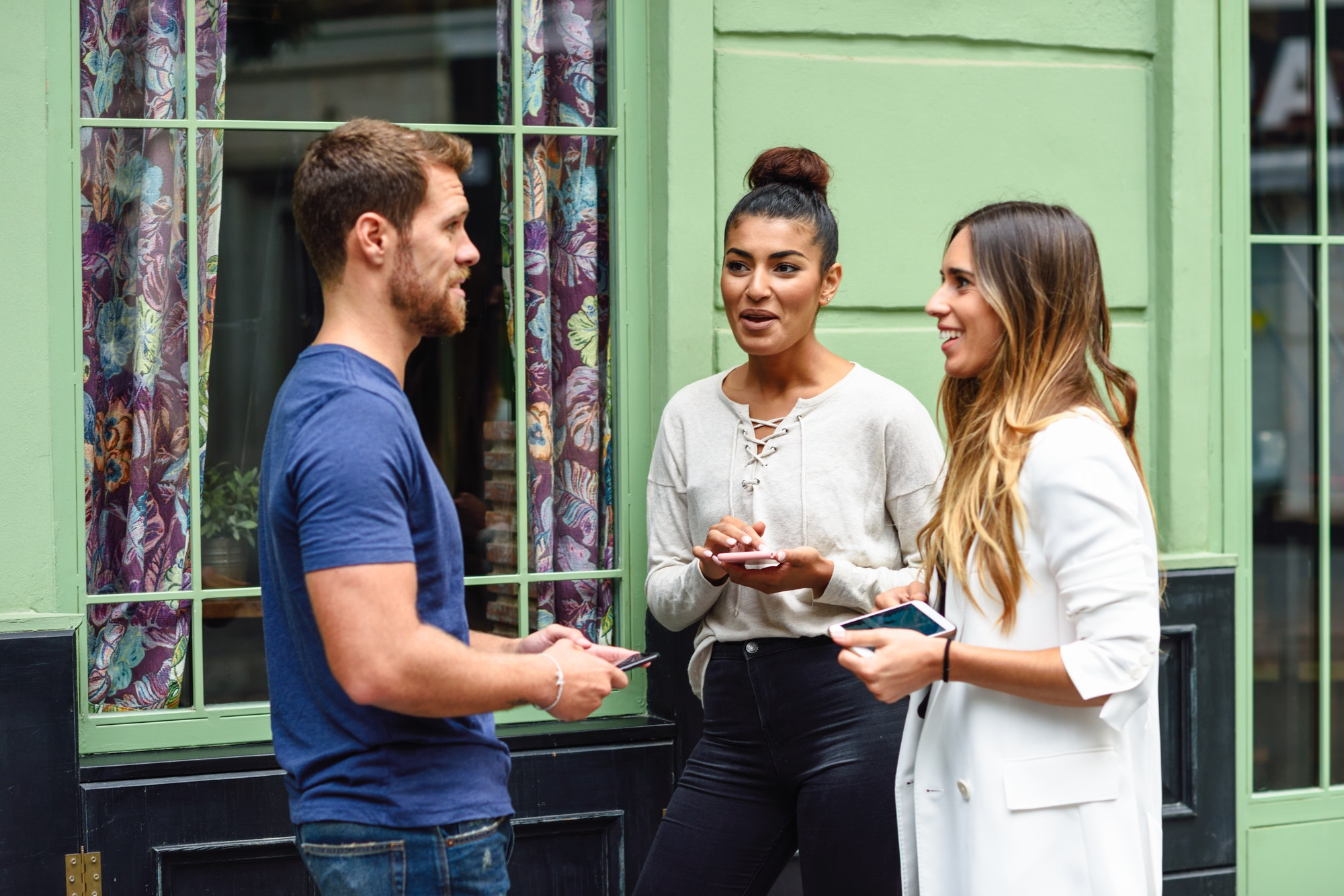 Three multiethnic people friends talking and smiling outdoors