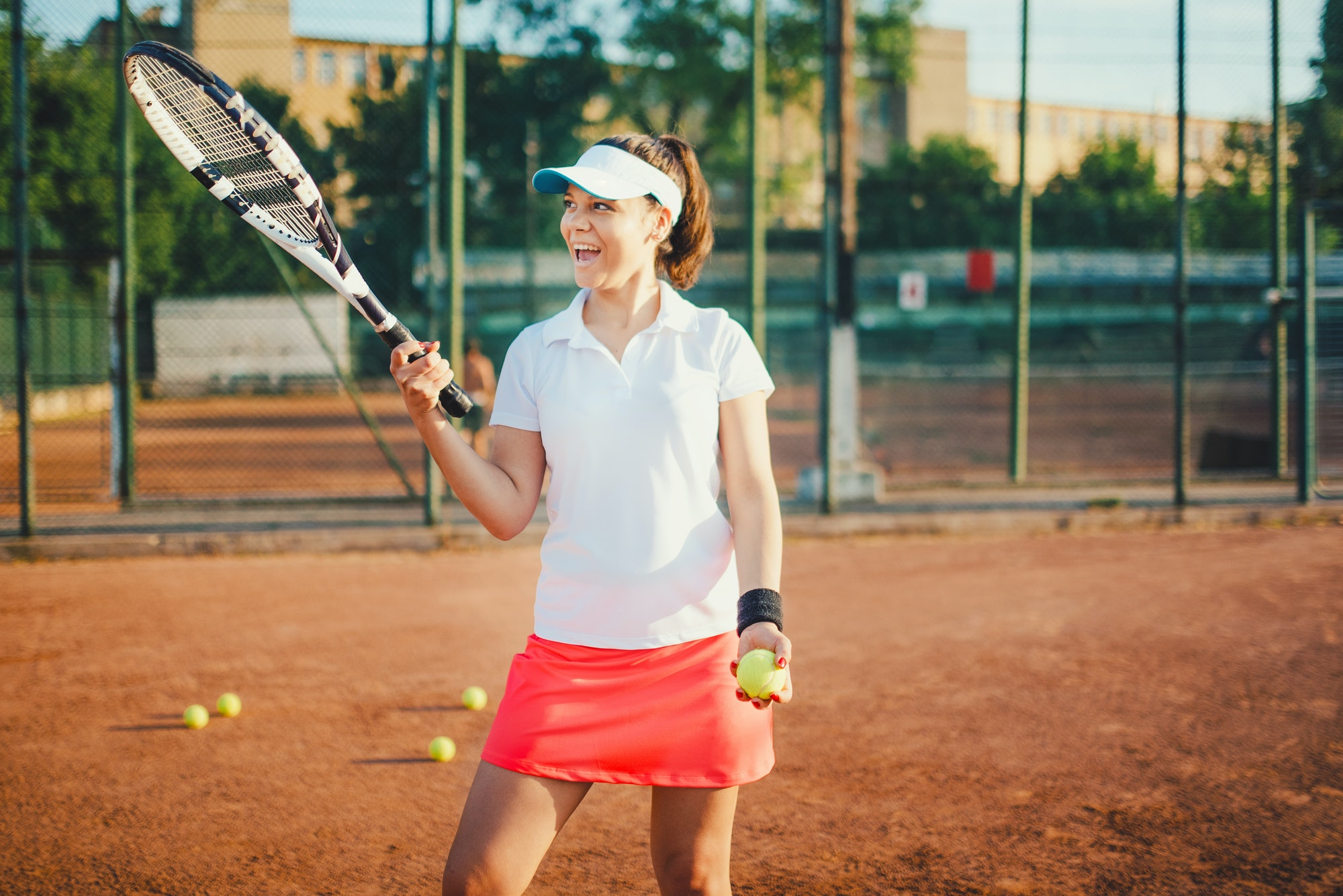 young tennis player, sportswoman on clay court with racquet and balls.